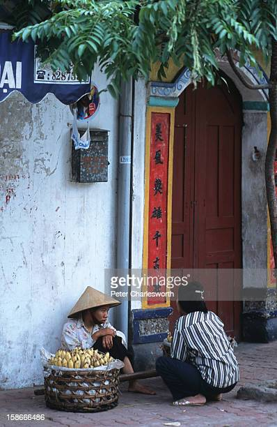A vendor selling bananas sits with her basket outside a doorway with Chinese lettering in one of the small streets of the old quarter north of Hoan...
