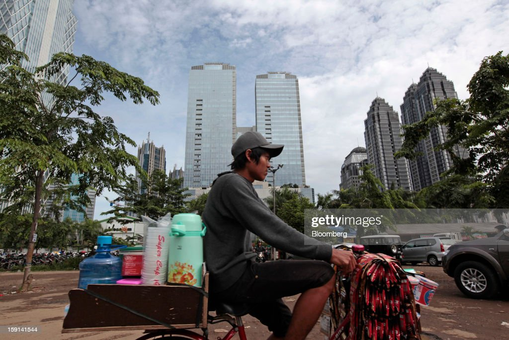 A vendor selling beverages rides his bicycle past the financial district of Jakarta, Indonesia, on Tuesday, Jan. 8, 2013. Indonesia's rupiah weakened by the most in six months on concern the government's failure to meet its spending target last year will hamper economic growth and damp demand for local assets. Photographer: Dimas Ardian/Bloomberg via Getty Images