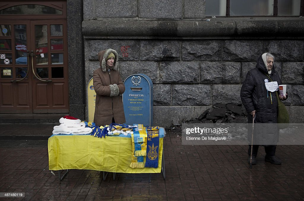 A vendor selling European Union and Ukrainian flags stands next to a begging woman near Independence Square after it was announced that Ukrainian President Viktor Yanukovych agreed to receive major economic assistance from Russia, on December 17, 2013 in Kiev, Ukraine. Thousands of protesters have taken to the streets since Ukrainian president Viktor Yanukovych announced a decision to suspend a trade and partnership agreement with the European Union and raised concerns that the nation could be poised to enter a customs union with Russia.