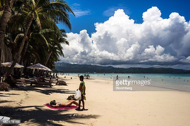 A vendor selling fruit approaches a tourist sunbathing on White Beach in Boracay the Philippines on Wednesday July 29 2015 The Philippines an...