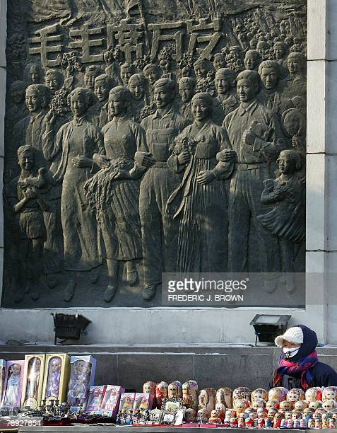 A vendor selling Russian stacked dolls or matryoshka awaits customers beside a mural near the Flood Control Monument in Harbin 12 January 2008 in...