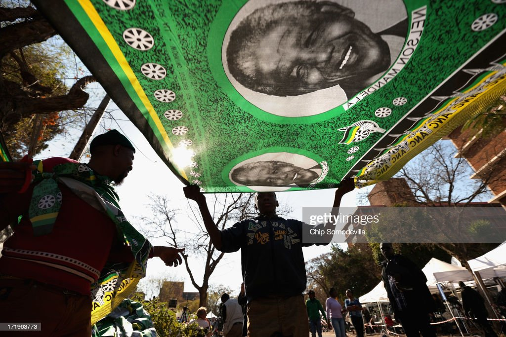 A vendor sells fabric with the image of former South African President Nelson Mandela outside the Mediclinic Heart Hosptial where Mandela is being treated for a recurring lung infection June 30, 2013 in Pretoria, South Africa. The anti-apartheid icon and Nobel Peace Prize laureate has been in the hospital for three weeks where his condition has been described as 'critical but stable.'