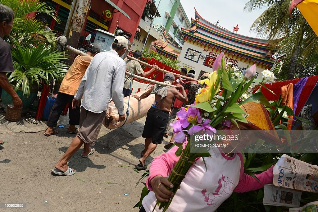 A vendor sells flowers while workers carry a giant candle to a Buddhist temple in the Indonesian capital city of Jakarta on February 8, 2013 as the Muslim majority country's minority Chinese-Indonesians prepares to celebrate the Chinese Lunar New Year. The 'Year of the Snake' falls across the region on February 10, 2013. AFP PHOTO / ROMEO GACAD