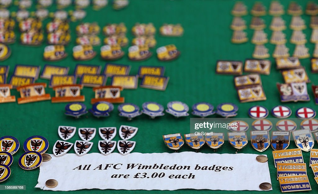 A vendor sells football pin badges outside AFC Wimbledon's stadium before the npower League Two match between AFC Wimbledon and Aldershot Town at the Cherry Red Records Stadium on November 17, 2012 in Kingston upon Thames, England. on December 1, 2012 League Two AFC Wimbledon, the football club formed in 2002 by supporters unhappy with their club's relocation to Milton Keynes, will play an FA Cup tie against League One Milton Keynes Dons, which Wimbledon F.C. controversially became.
