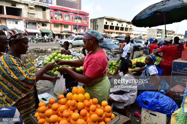 A vendor sells fruit at the large market of Adjame a popular district of Abidjan on August 10 2017 The Ivorian government in a council of ministers...