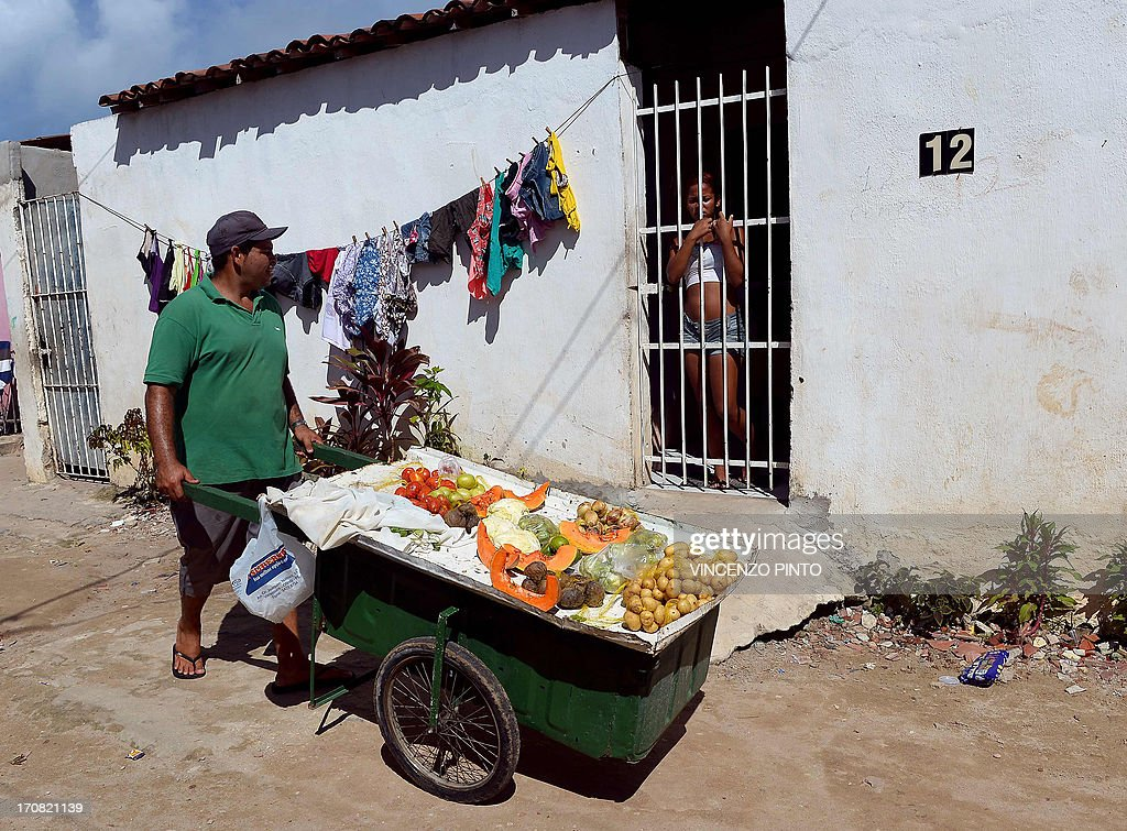 A vendor sells fruits and vegetables in a shantytown of Olinda, about 18 km from Recife in northeastern Brazil, on June 18, 2013 during the FIFA Confederations Cup Brazil 2013 football tournament. The historic centre of Olinda is listed as an UNESCO World Heritage Site.