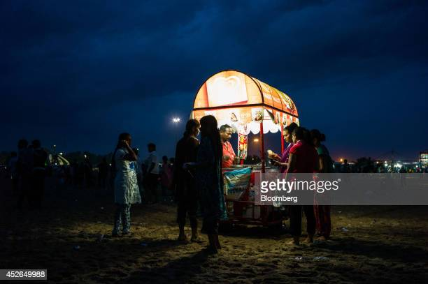 A vendor sells icecream to customers on Marina Beach in Chennai Tamil Nadu India on Sunday July 20 2014 Optimism about a revival in Asias...