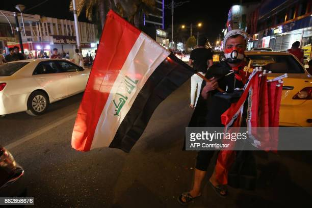 A vendor sells Iraqi flags as people gather in the street in the city of Kirkuk on October 18 after Iraqi government forces retook almost all the...