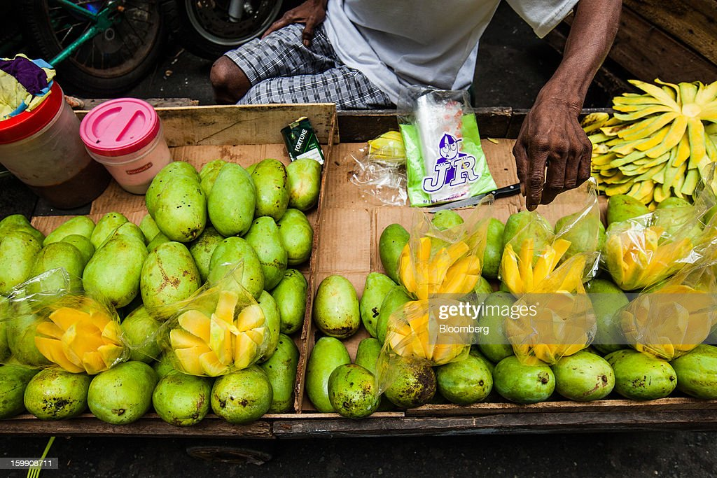 A vendor sells mangoes at the Divisoria market in Manila, the Philippines, on Tuesday, Jan. 22, 2013. Philippine government bonds advanced on speculation the central bank will hold its benchmark interest rate at a record low at a meeting tomorrow, supporting demand for the nation's debt. Photographer: Julian Abram Wainwright/Bloomberg via Getty Images