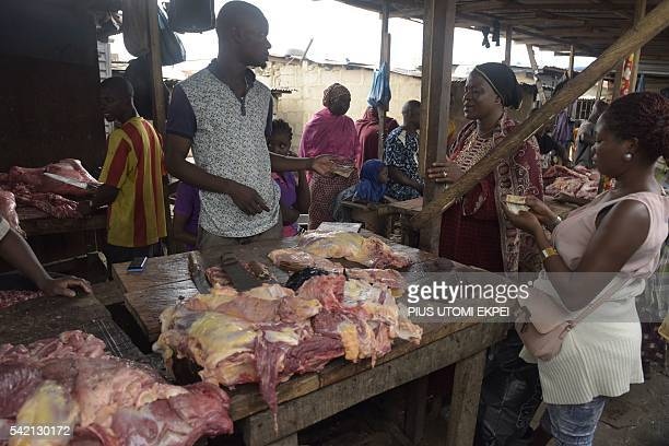 A vendor sells meat to clients at Magboro market in southwest Nigeria Ogun State on June 21 2016 Ordinary Nigerians are feeling the full effects of...