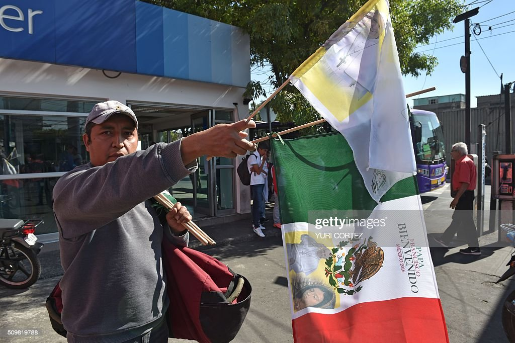 A vendor sells Mexican flags with the image of Pope Francis before his arrival in Mexico City on February 12, 2016. Pope Francis will arrive in Mexico on Friday, where he will visit until February 17. AFP PHOTO / YURI CORTEZ / AFP / YURI CORTEZ