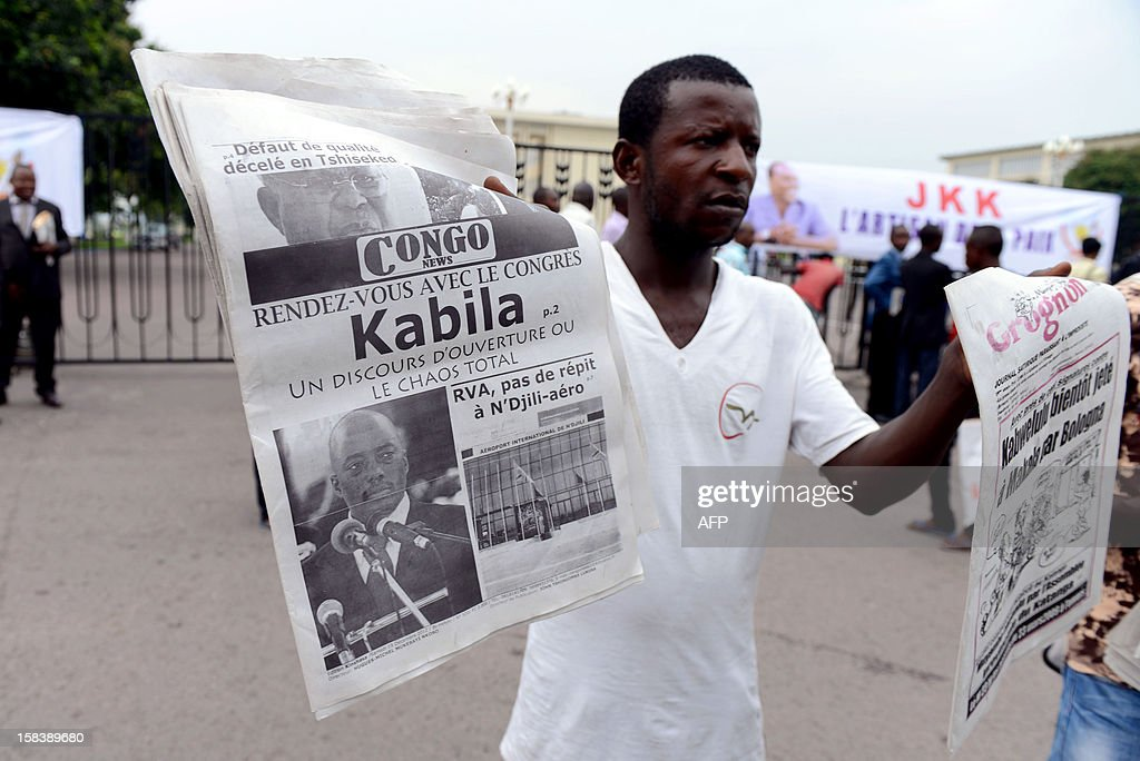 A vendor sells newspapers announcing Democratic Republic of Congo President Joseph Kabila's speech on December 15, 2012 outside Kinshasa's People Palace. Kabila on December 15 vowed that defence would be a top priority for his government after the recent brief rebel takeover of a key city in the country's volatile east.