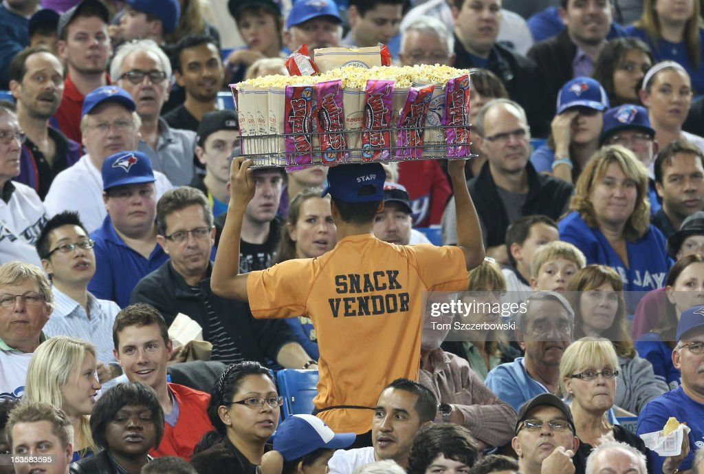 A vendor sells popcorn as fans watch the Toronto Blue Jays MLB game against the Minnesota Twins on October 3, 2012 at Rogers Centre in Toronto, Ontario, Canada.