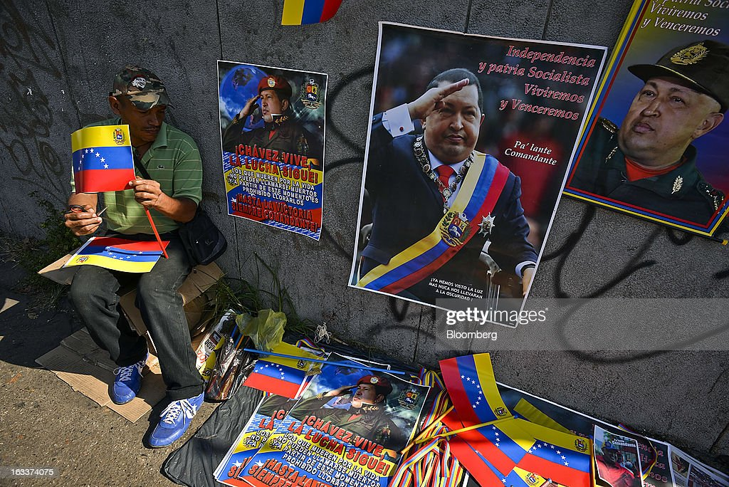 A vendor sells posters and flags during the funeral for Venezuelan President Hugo Chavez in Caracas, Venezuela, on Friday, March 8, 2013. Allies of Venezuela's Hugo Chavez paid their final respects to the firebrand socialist leader at a state funeral that marked the emotional high point of a week of tributes preceding a snap election to choose his successor. Photographer: Meridith Kohut/Bloomberg via Getty Images