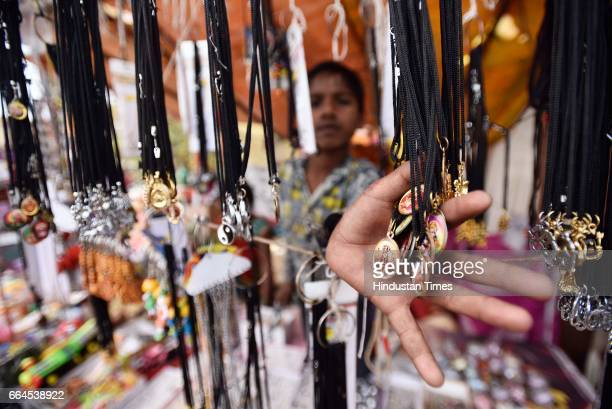 A vendor sells religious items outside Kalkaji Mandir on Asthami the eighth day of the festival of Navratri on April 4 2017 in New Delhi India...
