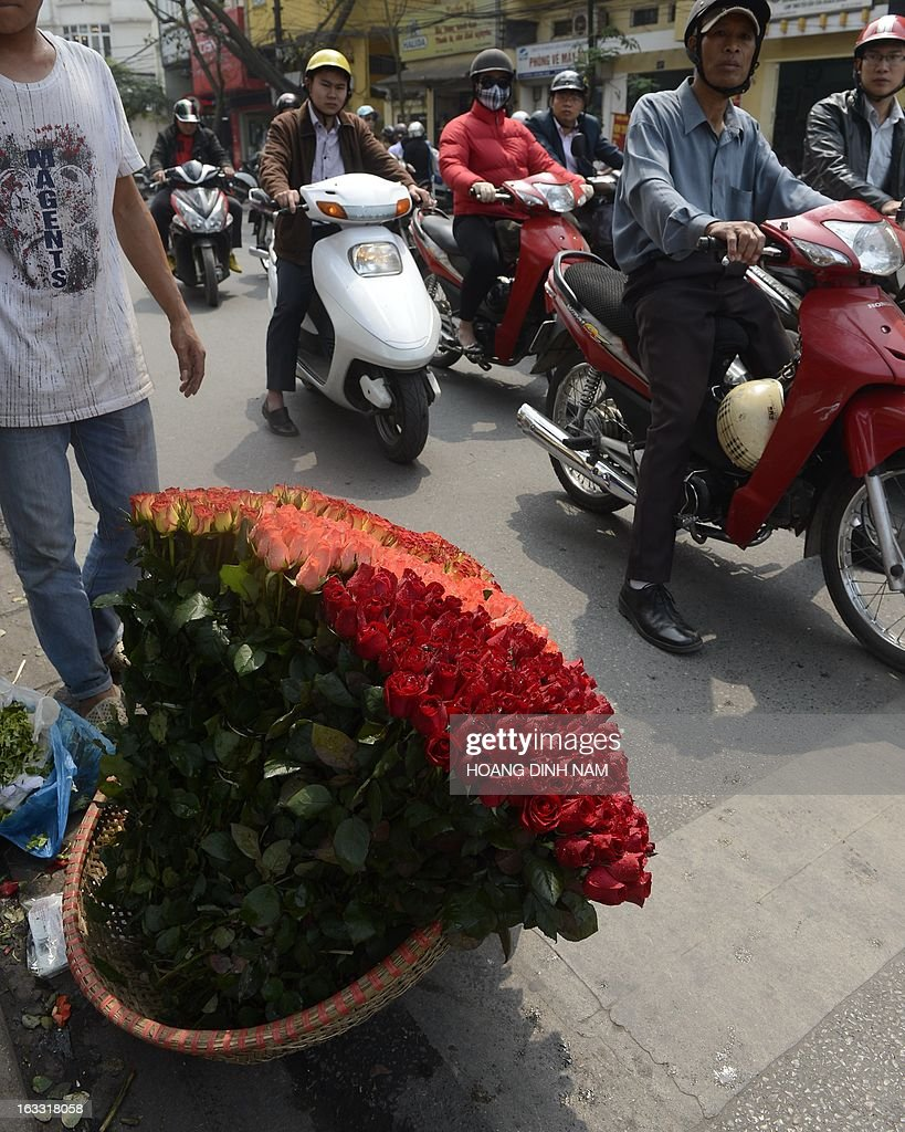 A vendor sells roses at a street corner as Vietnamese celebrate the International Women's Day in Hanoi on March 8, 2013. The day is a good business opportunity for florists with a sharp rise of flowers's prices, especially for roses. AFP PHOTO/HOANG DINH Nam