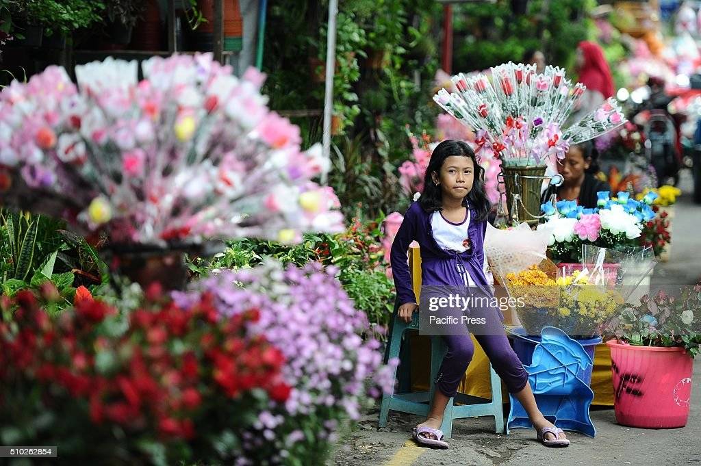A vendor sells roses at a traditional flower market during Valentines Day Roses chocolates Teddy Bears Hello Kitty heart toys candles and cards are...