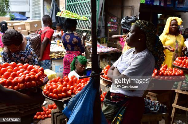 A vendor sells tomatoes at the large market of Adjame a popular district of Abidjan on August 10 2017 The Ivorian government in a council of...
