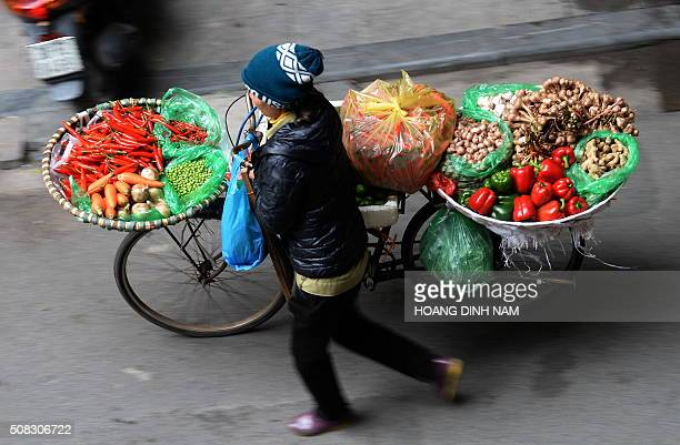 TOPSHOT A vendor sells vegetables along a street in downtown Hanoi on February 4 2016 as Vietnamese prepare to celebrate the Lunar New Year or Tet...