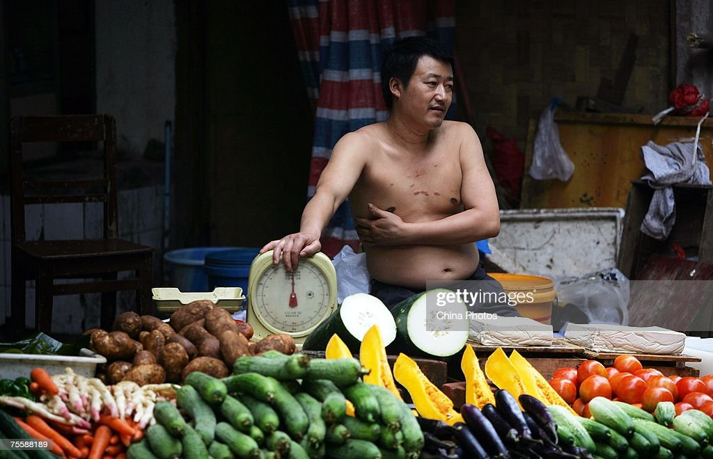 A vendor sells vegetables at a market on July 22 2007 in Chongqing Municipality China According to state media China admitted its supervision of food...