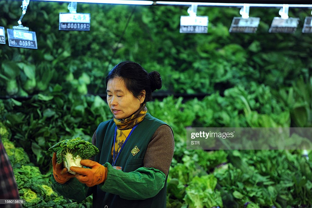 A vendor sells vegetables at a supermarket in Hefei, east China's Anhui province on December 9, 2012. China's inflation rate accelerated slightly to 2.0 percent in November, the National Bureau of Statistics said on December 9. CHINA OUT AFP PHOTO