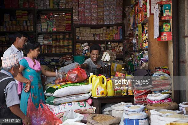 A vendor serves customers at the Kali Mati wholesale market in Kathmandu Nepal on Sunday May 31 2015 Nepal's gross domestic product will probably...