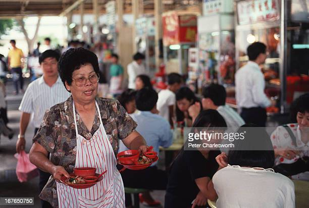 A vendor serves food at the 'Hawker' center at Newton Circus For reasons of hygiene the Government of Singapore banned street hawkers instead setting...