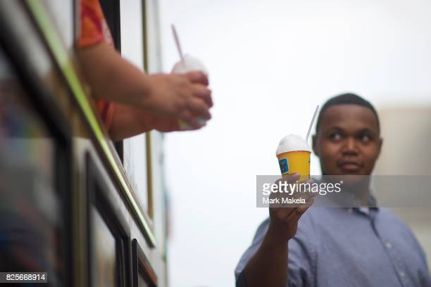 A vendor serves free shaved iced to job seekers waiting in line during an Amazon jobs fair at the Amazon Fulfillment Center on August 2 2017 in...