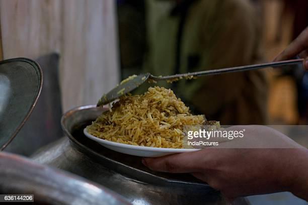 Vendor Serving Chicken Biryani In Plate