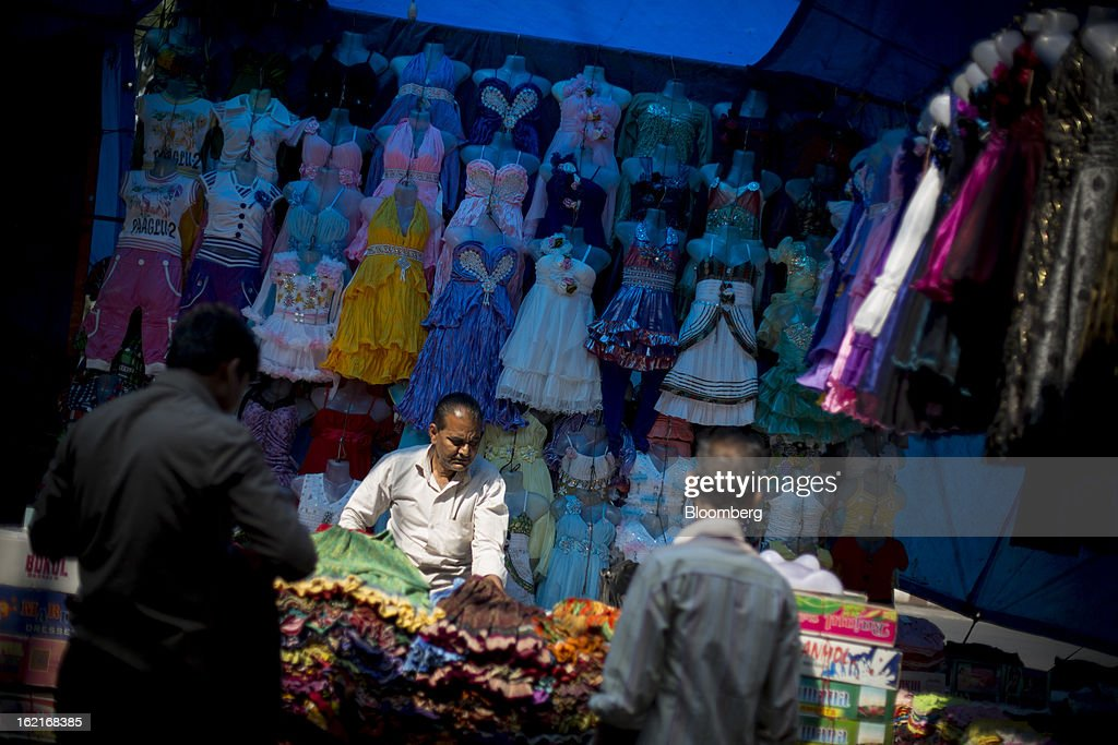A vendor sets up a clothing stall in the New Market area of Kolkata, India, on Tuesday, Feb. 19, 2013. India's slowest economic expansion in a decade is limiting profit growth at the biggest companies even as foreigners remain net buyers of the nation's stocks, according to Kotak Institutional Equities. Photographer: Brent Lewin/Bloomberg via Getty Images