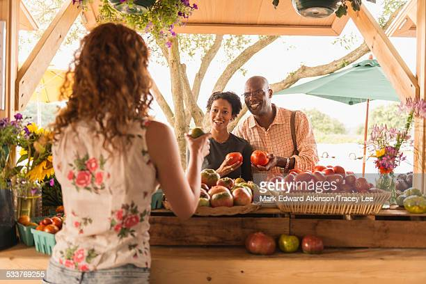 Vendor showing produce to couple at farmers market