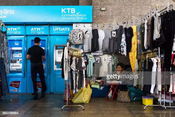 A vendor sits at a clothing stall set up beside a Krung Thai Bank Pcl Automated Teller Machines in the Phaya Thai District of Bangkok Thailand on...
