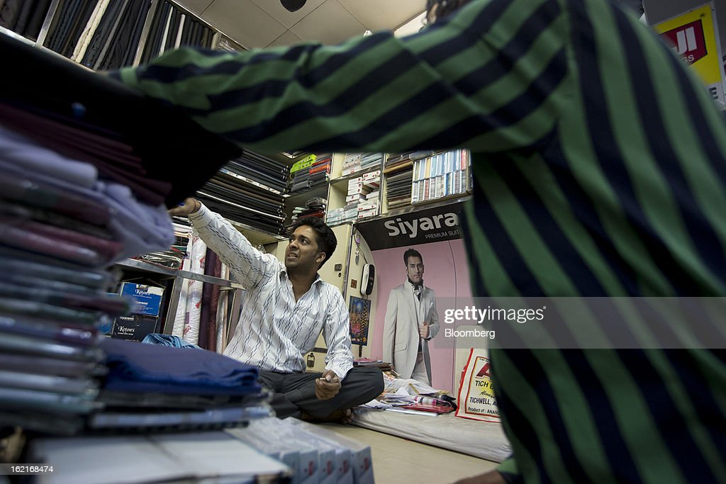A vendor sits in a fabric store in the Burrabazar area of Kolkata, India, on Tuesday, Feb. 19, 2013. India's slowest economic expansion in a decade is limiting profit growth at the biggest companies even as foreigners remain net buyers of the nation's stocks, according to Kotak Institutional Equities. Photographer: Brent Lewin/Bloomberg via Getty Images