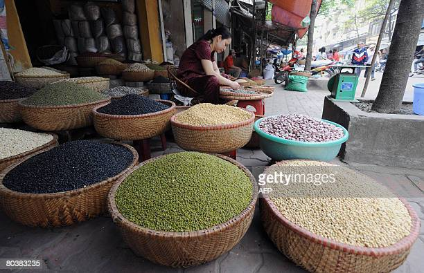 A vendor sits sorting grains next to baskets of different cereals at a local market in downtown Hanoi on March 26 2008 Vietnamese consumer prices...