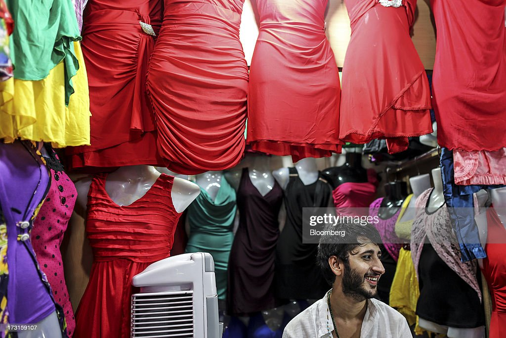 A vendor sits waiting for customers at his clothing stall in the suburb of Bandra in Mumbai, India, on Saturday, July 6, 2013. India's consumer price index (CPI) figures for June are scheduled to be released on July 12. Photographer: Dhiraj Singh/Bloomberg via Getty Images