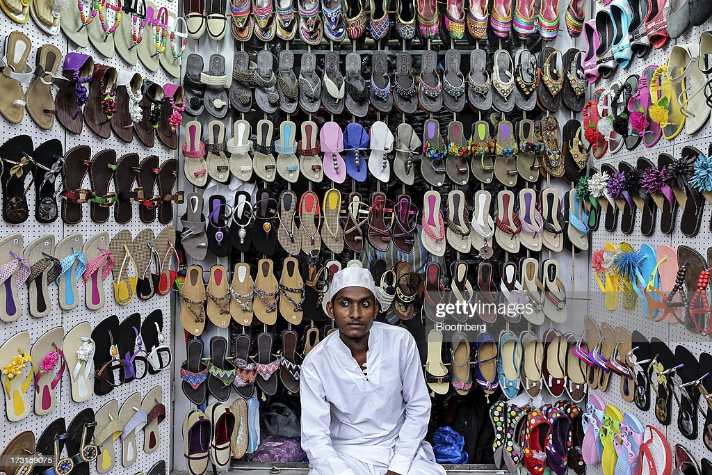 A vendor sits waiting for customers at his shoe stall in the suburb of Bandra in Mumbai, India, on Saturday, July 6, 2013. India's consumer price index (CPI) figures for June are scheduled to be released on July 12. Photographer: Dhiraj Singh/Bloomberg via Getty Images