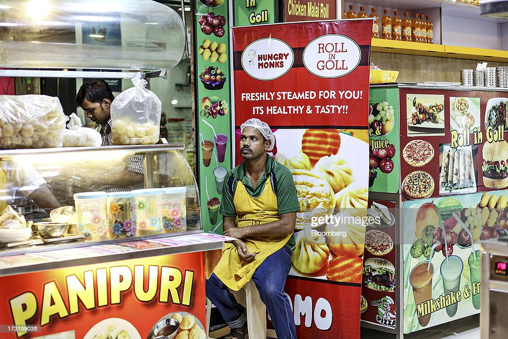 A vendor sits waiting for customers beside a panipuri stall at a food court in the suburb of Bandra in Mumbai, India, on Saturday, July 6, 2013. India's consumer price index (CPI) figures for June are scheduled to be released on July 12. Photographer: Dhiraj Singh/Bloomberg via Getty Images