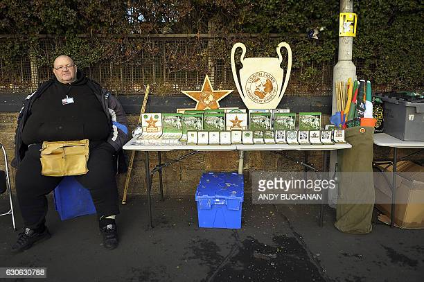 A vendor sits with his Celtic memorabilia outside Celtic Park in Glasgow on December 17 2016 before their Scottish Premiership football match against...