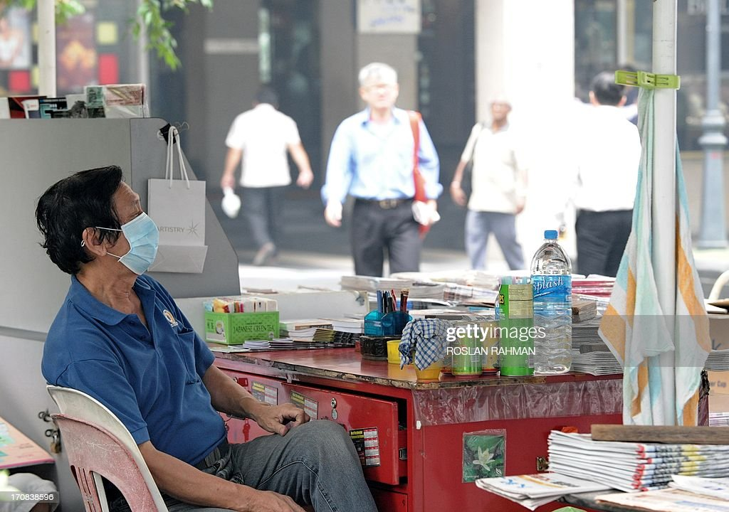 A vendor sits with his face covered with a mask as haze worsens in Singapore on June 19, 2013. Singapore's Pollutant Standards Index again shot above the 'unhealthy' threshold of 152. AFP PHOTO / Roslan Rahman