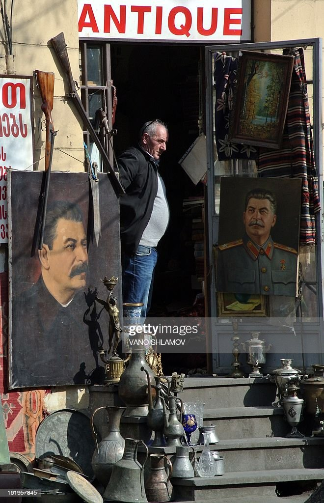 A vendor stands at the entrance of his antique shop offering portraits of Joseph Stalin on February 18, 2013 in central Tbilisi.