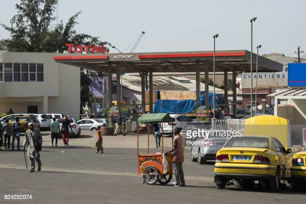 A vendor stands by a mobile juice cart in front of a gas station operated by Total SA in Dakar Senegal on Friday July 28 2017 Senegalese voters will...