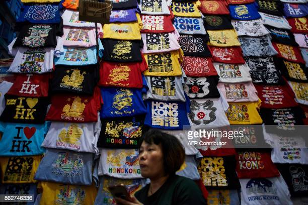 A vendor stands in front of her display of souvenir Tshirts in Hong Kong on October 18 2017 / AFP PHOTO / Anthony WALLACE