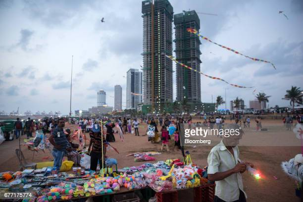 A vendor stands near a stall selling toys at Galle Face Green as the under construction ShangriLa Hotel Colombo stands in the background in Colombo...