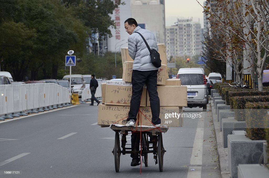 A vendor stands on a tricycle with his goods as he makes his way along a street in Beijing on November 22, 2012. China's manufacturing activity grew in November for the first time in 13 months, HSBC said on November 22, in a further sign of strength in the world's second-largest economy after a marked slowdown.