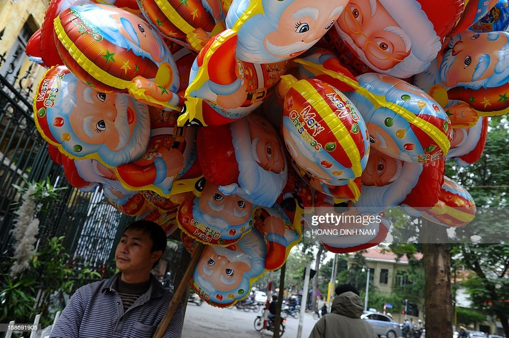 A vendor stands selling Santa Claus balloons outside a church in downtown Hanoi on December 24, 2012. Churches, shops, restaurants and shopping mails are being decorated in the Southeast Asian communist nation where some 6 million catholic community are preparing to celebrate Christmas. AFP PHOTO/HOANG DINH Nam