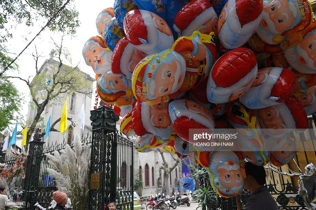 A vendor stands selling Santa Claus balloons outside a church (L) in downtown Hanoi on December 24, 2012. Churches, shops, restaurants and shopping mails are being decorated in the Southeast Asian communist nation where some 6 million catholic community are preparing to celebrate Christmas. AFP PHOTO/HOANG DINH Nam