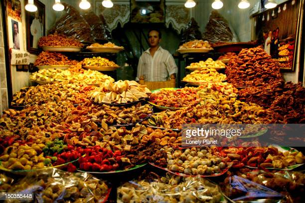 Vendor surrounded by piles of sweets in souk stall.