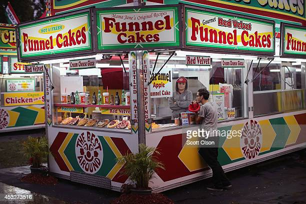 A vendor takes a food order at a concession stand at the Iowa State Fair on August 6 2014 in Des Moines Iowa The fair opens to the public on August 7...
