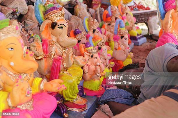 A vendor takes a nap as he sells the idols of elephantheaded Hindu god Lord Ganesh ahead of Ganesha Chathurthi festival on August 24 2014 in Noida...