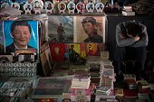 TOPSHOT A vendor takes a nap next to posters showing the late Chinese chairman Mao Zedong and Chinese President Xi Jinping at a market in Beijing on...